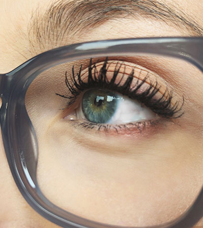 Close up eye and eyeglass lens